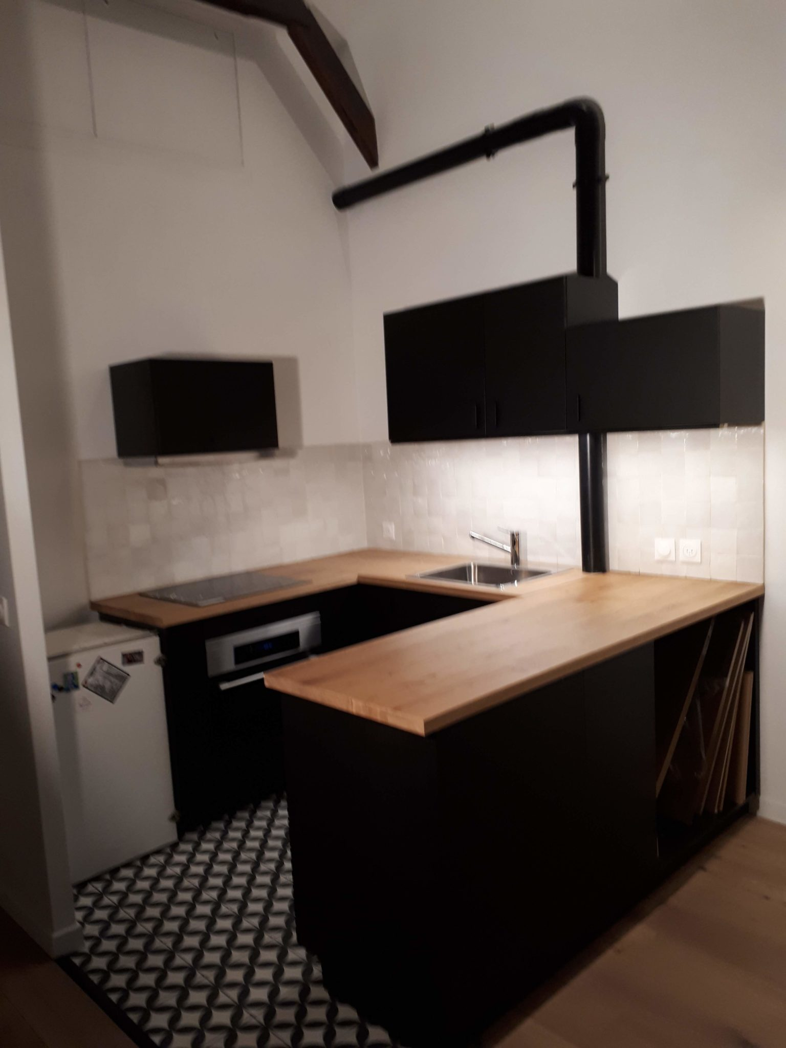 Cuisine Paris 14ème. carreaux de ciment en damier, plan chêne, meubles noirs